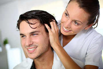 Young man discussing hair replacement prices with hair stylist