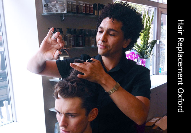 Male stylist demonstrating hair replacement systems at a hairdressers in Oxford, Oxfordshire, UK.