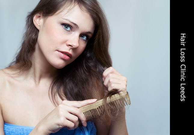 Attractive woman combing hair following the fitting of hair replacement in Leeds
